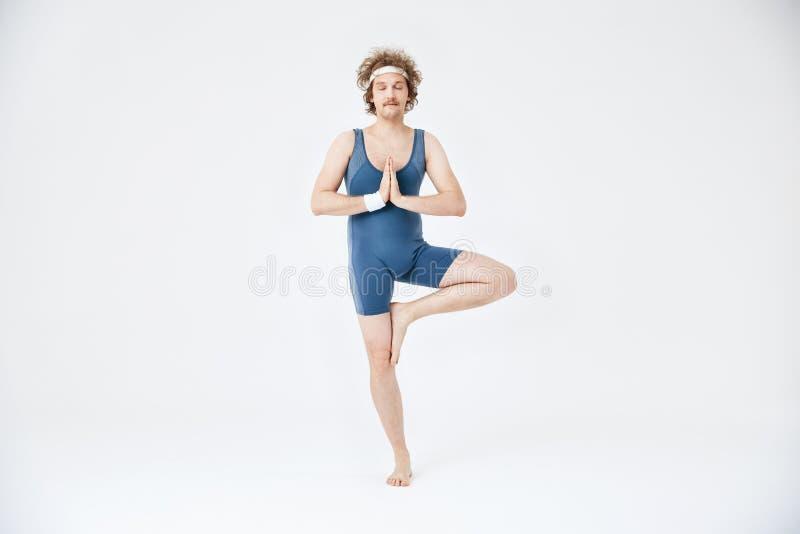 Mann in übendem Yoga der im altem Stil Sportkleidungs Vrikshasana mit den Augen geschlossen lizenzfreie stockbilder