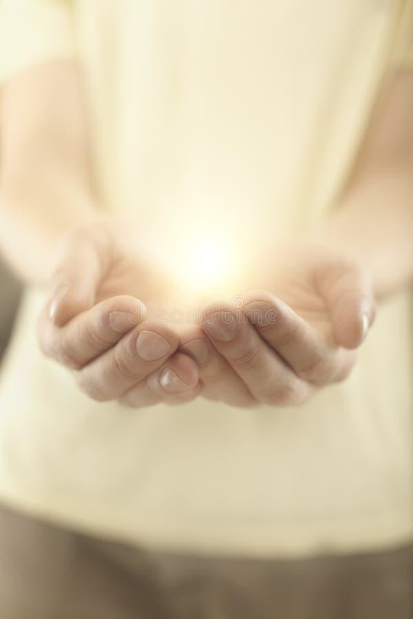 Mann übergibt Holdingstrahlen der glühenden Leuchte. lizenzfreie stockfotografie