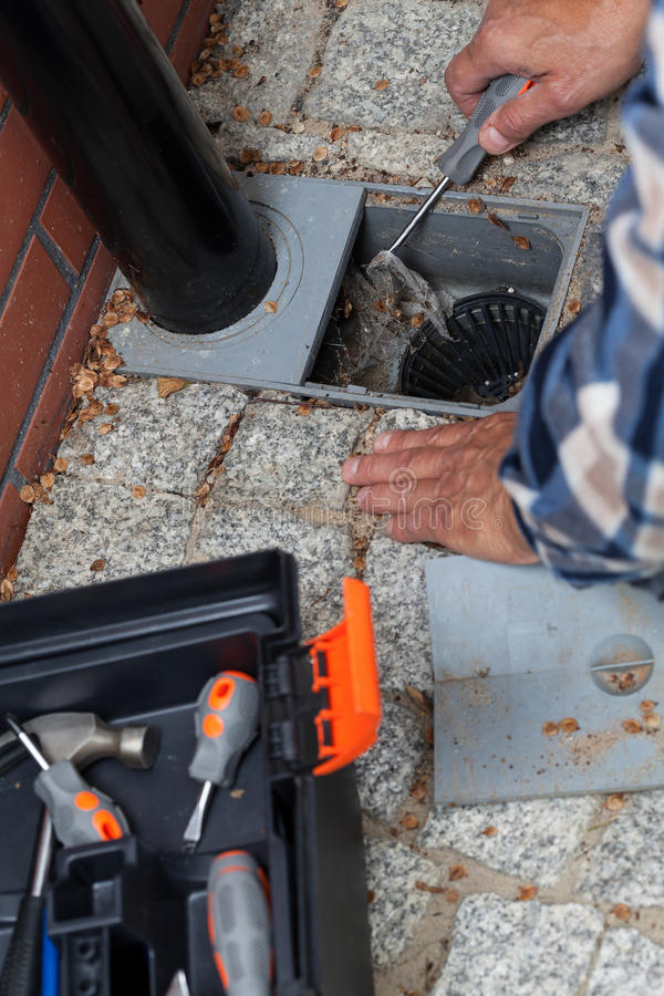 Mann übergibt Reinigungspflasterungs-Ablaufloch stockfoto