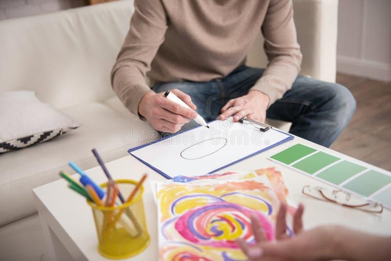 Mann übergibt Zeichnung während der Therapie lizenzfreie stockbilder