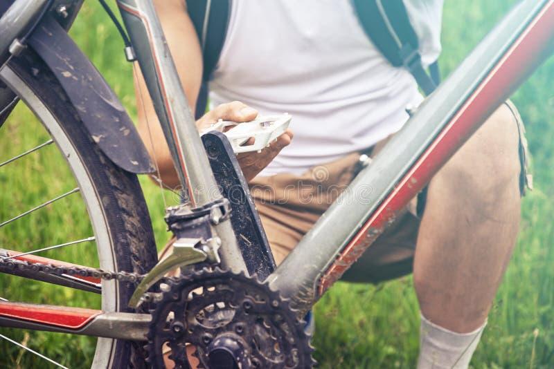 Mann überprüft Pedal des Fahrrades lizenzfreie stockbilder