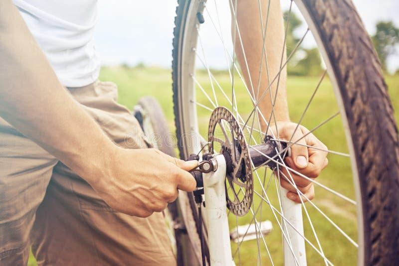 Mann überprüft Rad des Fahrrades lizenzfreies stockbild