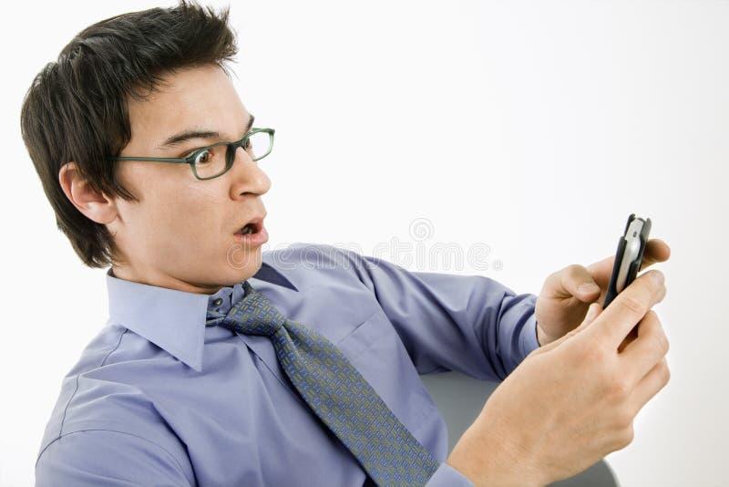 Mann überrascht an der Textmeldung. stockbild
