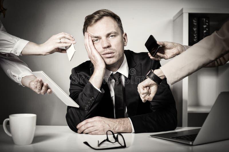 Mann überwältigt mit Aufgaben und Verantwortung bei der Arbeit stockbild