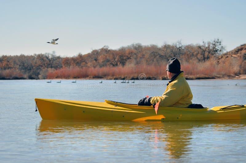Mann in überwachenden Vögeln des Kajaks lizenzfreies stockfoto