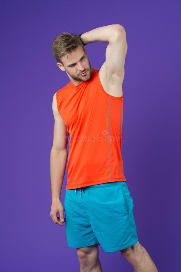Mann überzeugt in seinem Antitranspirationsmittel Kerl überprüft die trockene Achselhöhle, die mit gesunder Haut zufrieden gestel stockfoto
