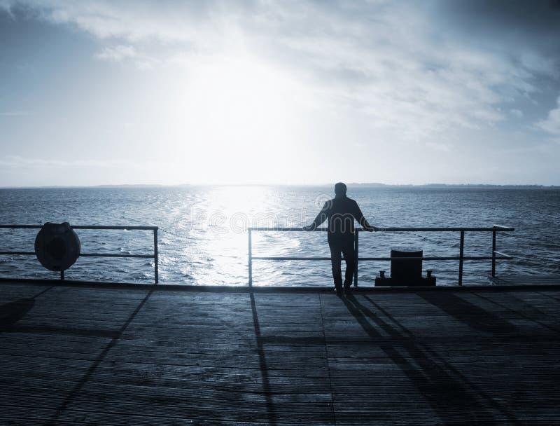 Mann allein bleiben auf Seebrücke und passen den erstaunlichen Sonnenaufgang auf stockfotografie