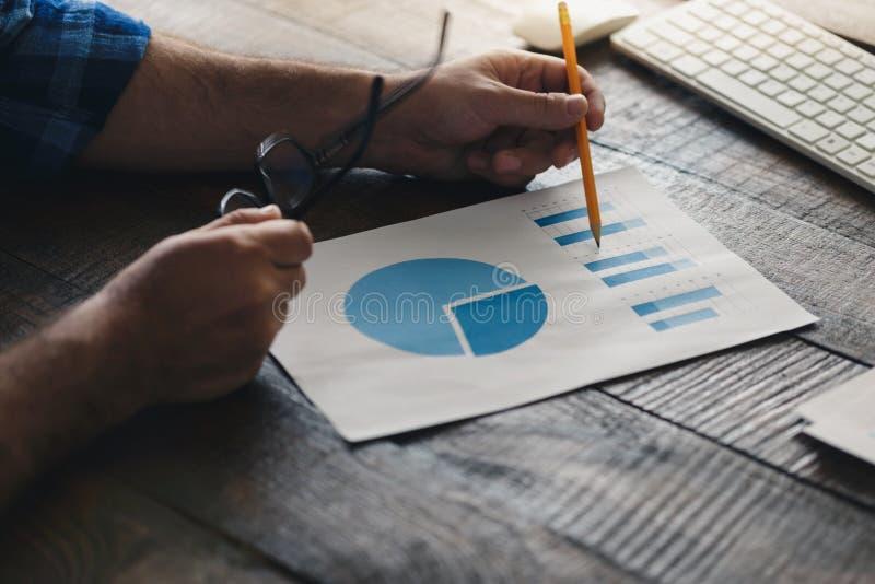 Mann analysiert die Daten und die Diagramme im Büro lizenzfreie stockbilder