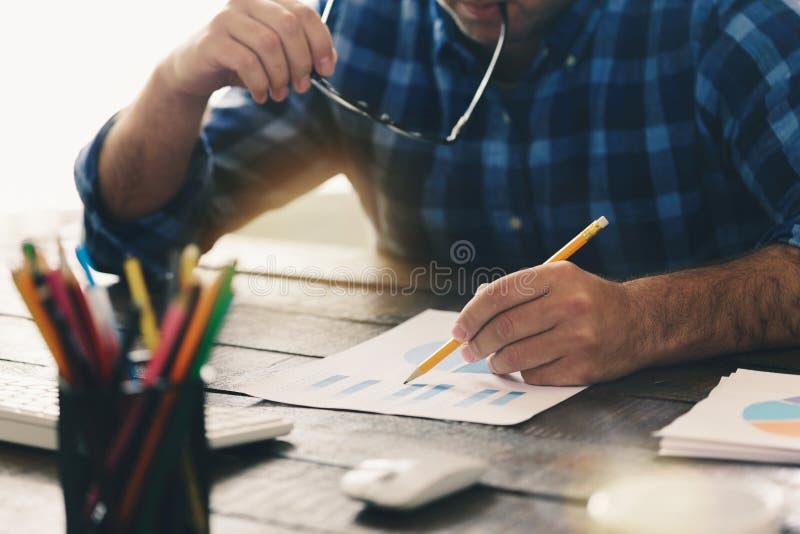 Mann analysiert die Daten und die Diagramme im Büro lizenzfreie stockfotografie