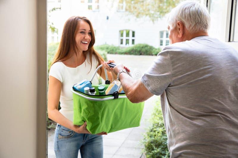 Mann-Angebothilfe zu seinen Tochter-tragenden Lebensmittelgesch?ften lizenzfreie stockfotografie