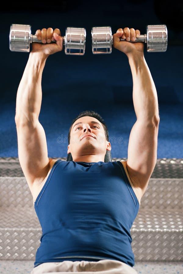 Mann anhebendes dummbell in der Gymnastik stockbilder
