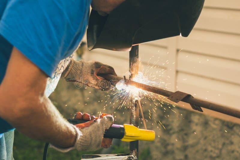 Mann arbeitet als elektrischer Schweißer in seinem Sommerhäuschen lizenzfreie stockfotografie