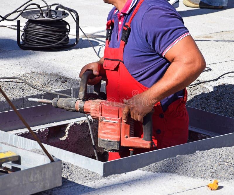 Mann arbeitet mit einem Bohrgerät an der Baustelle stockfoto