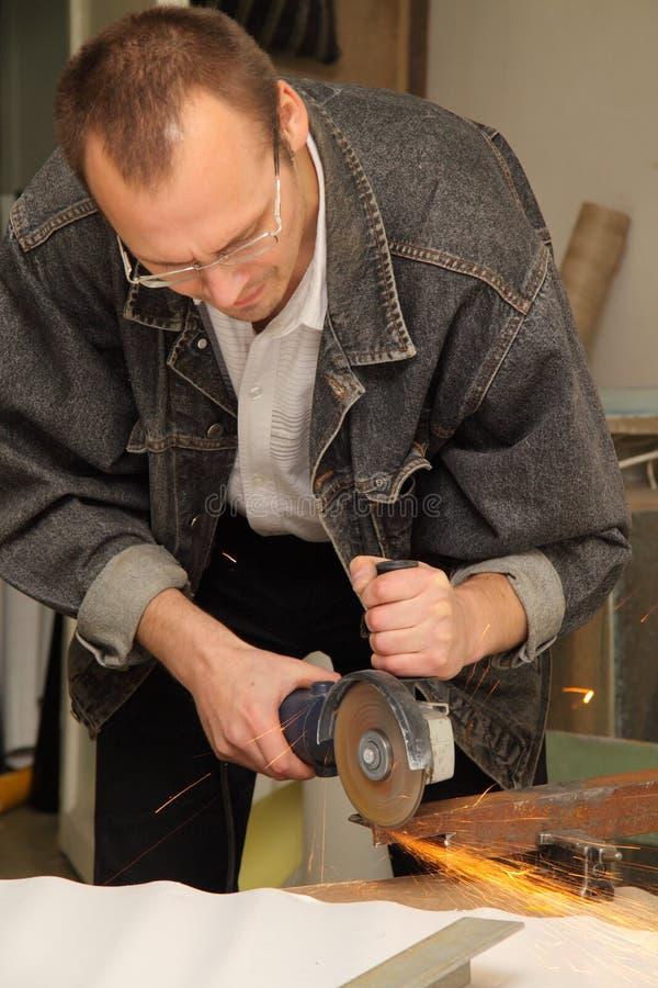 Mann arbeitet mit einer Zirkulationssäge im Studio lizenzfreie stockfotos
