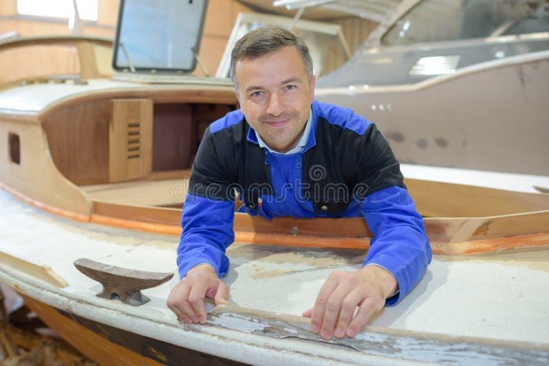 Mann am Arbeitsgebäudeboot lizenzfreies stockfoto