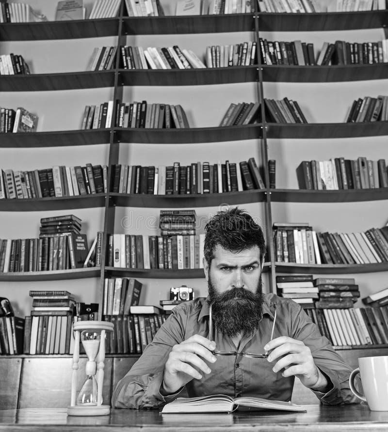 Mann auf beschäftigtem Gesichtslesebuch, Bücherregale auf Hintergrund Bildungs- und Wissenschaftskonzept Wissenschaftler sitzt be lizenzfreies stockfoto