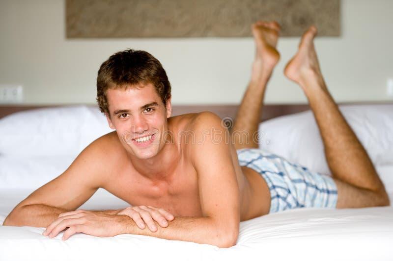 Mann auf Bett stockbilder
