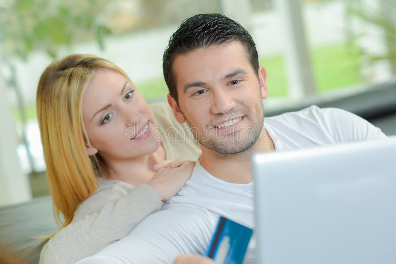 Mann auf dem Computer, der Kreditkartedame schaut über Schulter hält lizenzfreie stockfotos