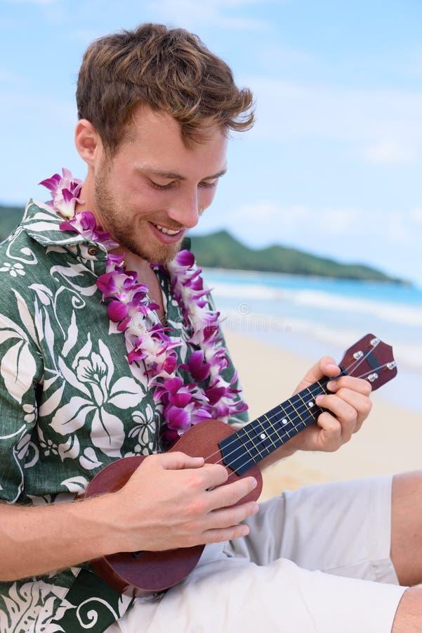 Mann auf dem hawaiischen Strand, der Ukulele auf Hawaii spielt lizenzfreie stockfotos
