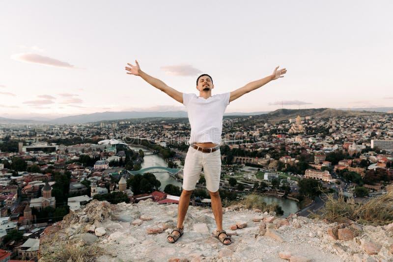 Mann auf dem Hintergrund des Panoramablicks von Tiflis stockbild