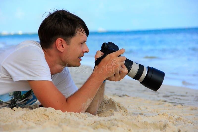 Mann auf dem karibischen Strand mit einer Kamera stockbilder