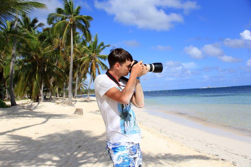 Mann auf dem karibischen Strand mit einer Kamera stockfoto