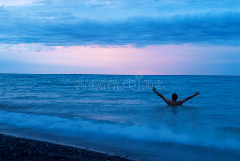 Mann auf dem Meer am Sonnenuntergang lizenzfreies stockbild