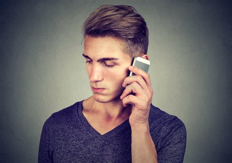 Mann auf dem Mobiltelefon mit Kopfschmerzen Umgekippter unglücklicher Kerl, der am Telefon spricht stockfotografie