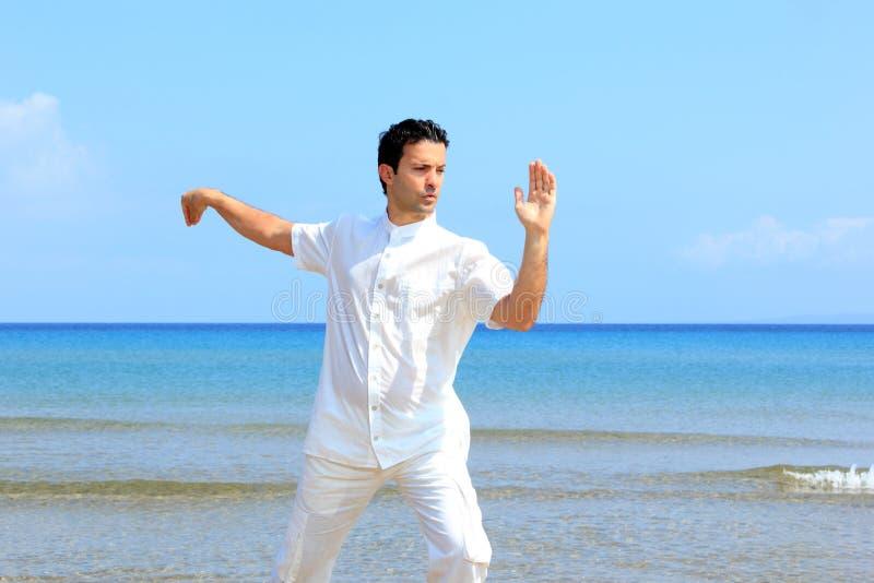 Mann auf dem Strand meditierend lizenzfreies stockbild