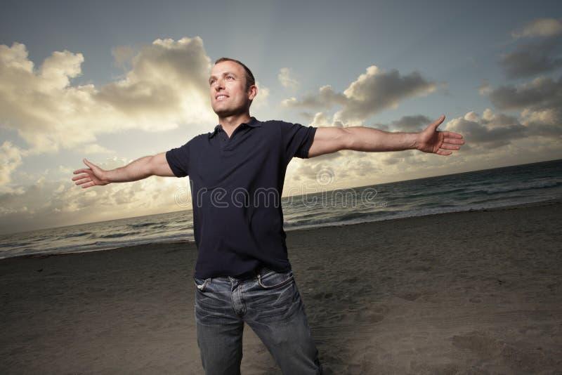 Mann auf dem Strand mit den Armen dehnte sich aus lizenzfreies stockbild