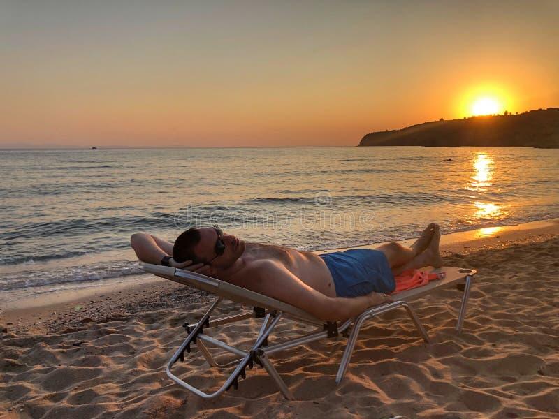 Mann auf dem Strand am Sonnenuntergang stockbild