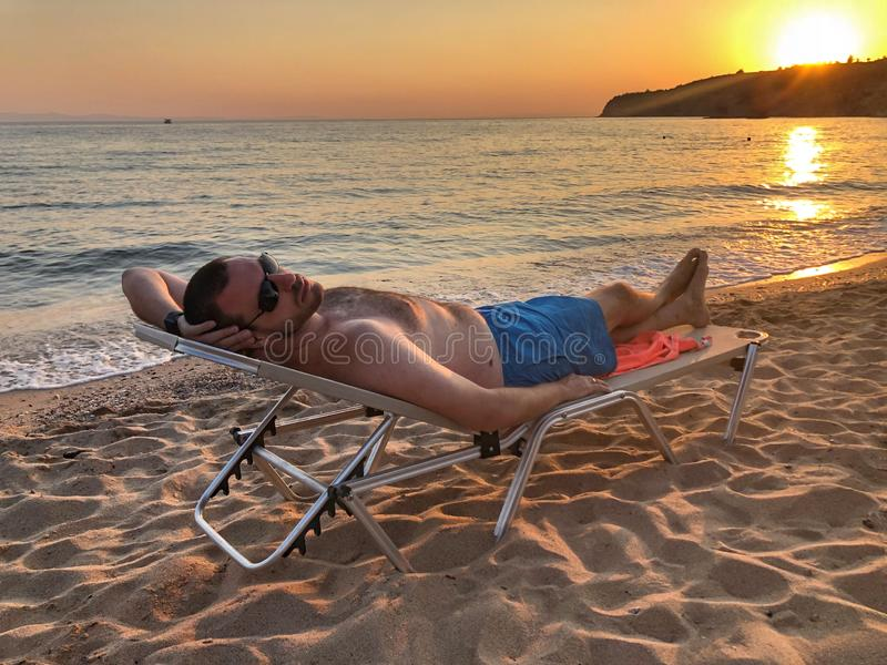 Mann auf dem Strand am Sonnenuntergang stockfotos