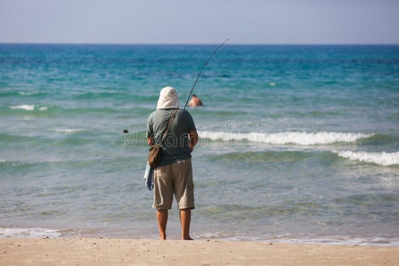 Mann auf dem Strandfischen stockfotos