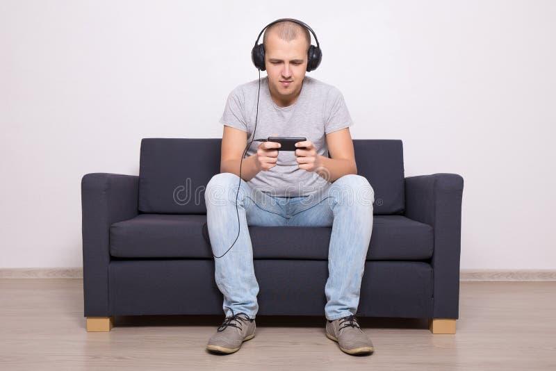 Mann auf der Couch, die Spiele spielt oder Film am Handy aufpasst stockfoto