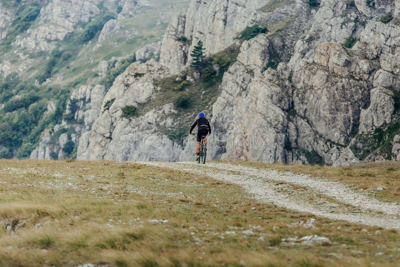 Mann auf der Mountainbike, die in Berge reitet lizenzfreie stockfotografie