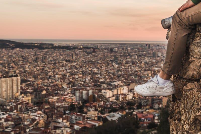 Mann auf die Oberseite eines Berges die Stadt aufpassend lizenzfreie stockfotos
