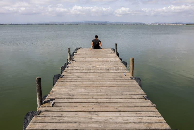 Mann auf einem Dock durch den See an Morgen Himmel lizenzfreies stockbild