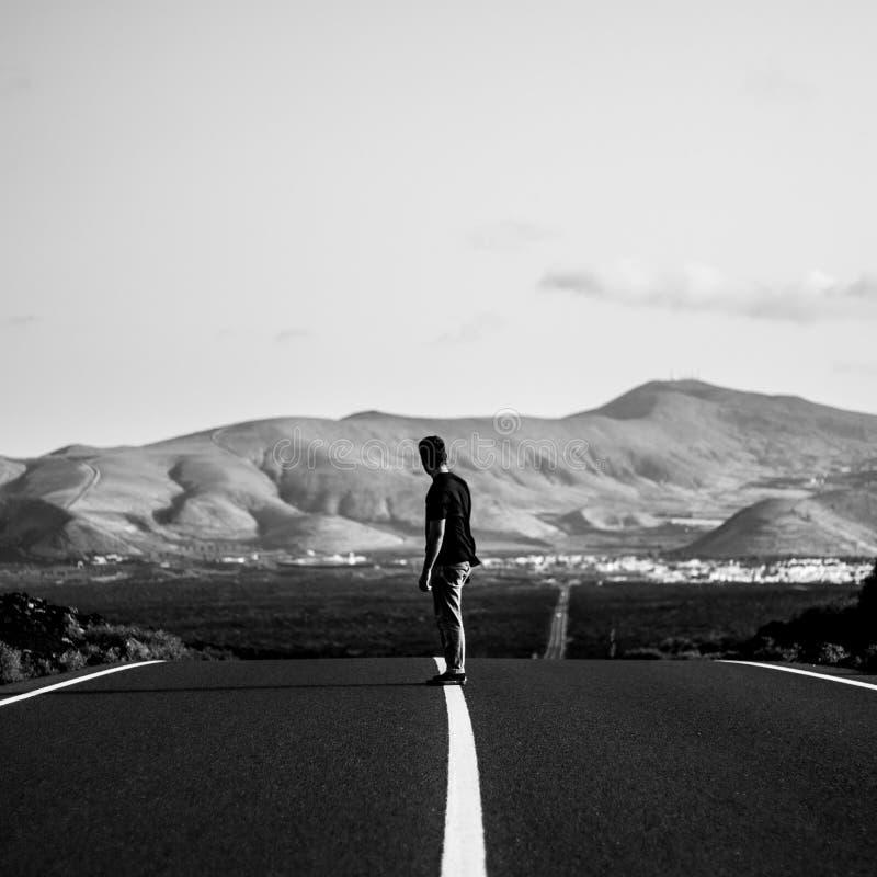 Mann auf einem Skateboardfahrerreiten auf einer leeren Landstraßenstraße mit überraschenden Hügeln im Hintergrund stockbild