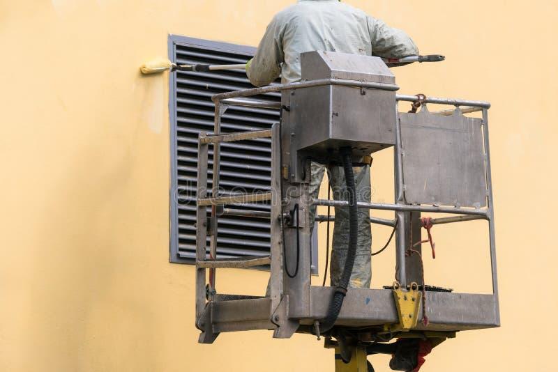 Mann auf einer anhebenden Plattform, welche die errichtende Wand mit einem Rollenaußenfreien malt Arbeitskraft auf einer Leiter g stockbilder