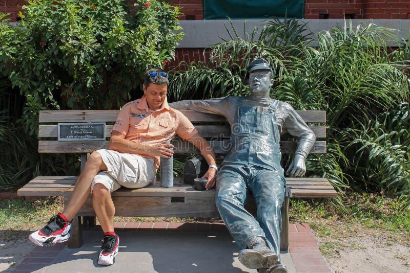 Mann auf einer Bank mit dem Skulptur ` Mittagspause ` durch J Seward Johnson auf Key West-Kunstmuseum- und -geschichtsskulptur Au lizenzfreie stockfotos