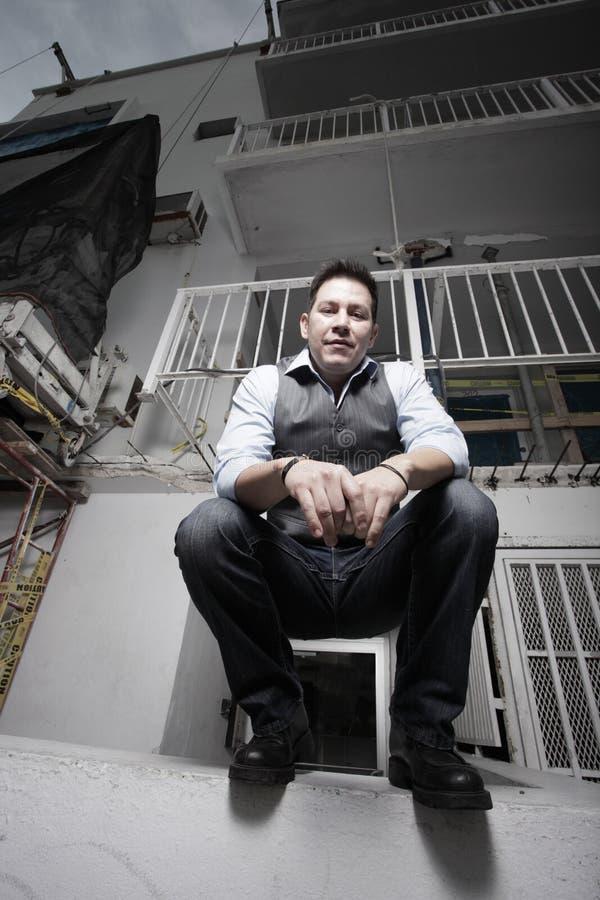 Mann auf einer Gebäudeleiste stockfotografie