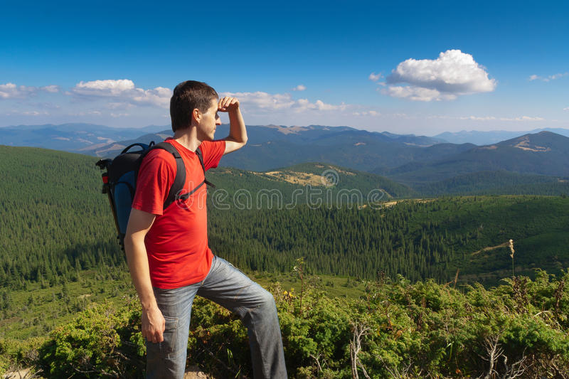 Mann auf einer Spitze der Berge und des Schauens der Landschaft lizenzfreies stockfoto