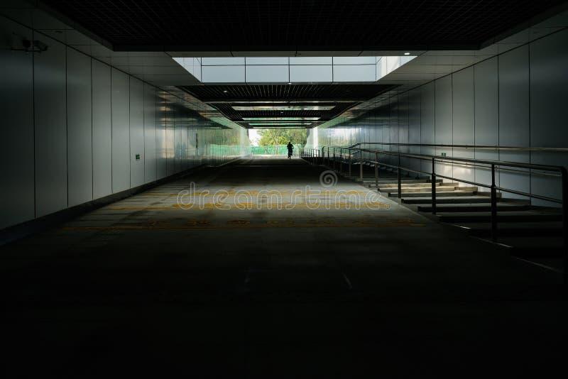 Mann auf Fahrrad am Eingang des Untertagestraßentunnels mit eingezäuntem p stockbilder