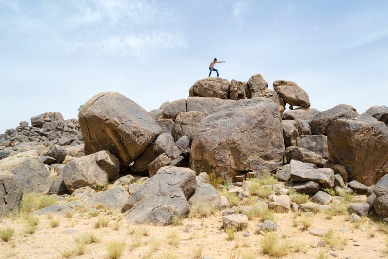 Mann auf Felsen etwas mit seinem Finger zeigend lizenzfreie stockfotos