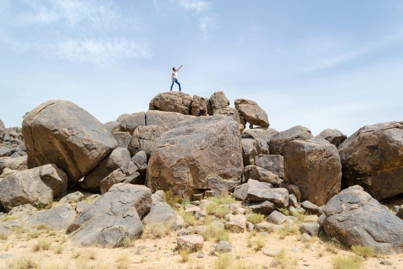 Mann auf Felsen seinen Finger auf den Himmel zeigend stockbild