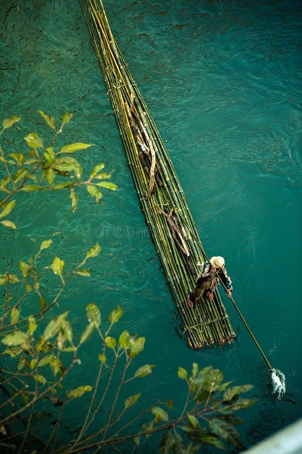 Mann auf grünem Bambusfloss stockfotografie