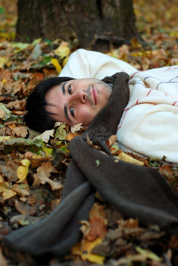 Mann auf Herbstblättern lizenzfreie stockfotos