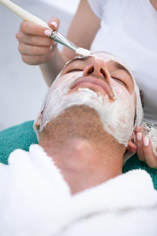 Mann auf kosmetischem Verfahren der Maske stockfoto