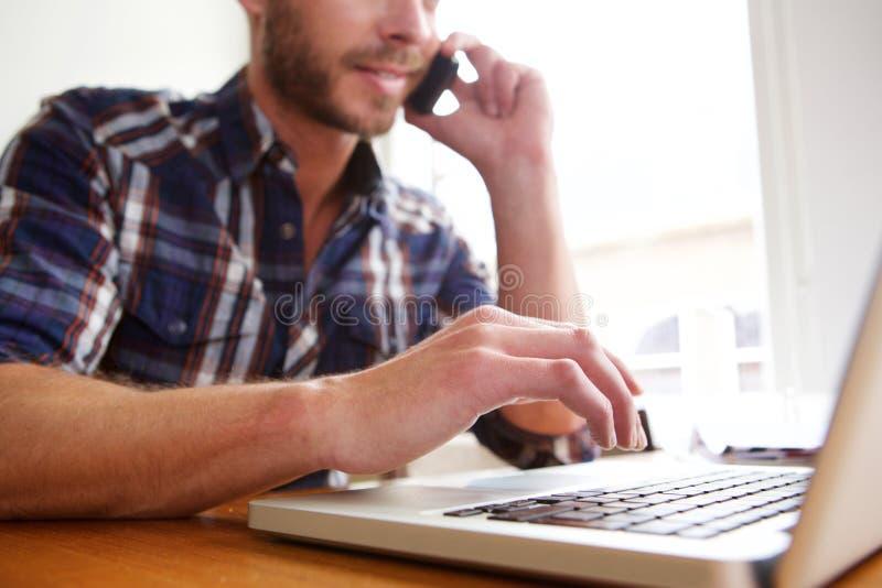 Mann auf Laptop-Computer und Unterhaltung am Telefon lizenzfreies stockfoto