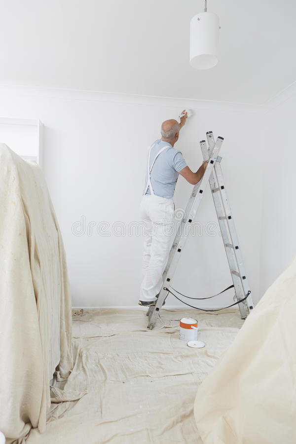 Mann auf Leiter inländischen Raum mit Pinsel verzierend stockfoto